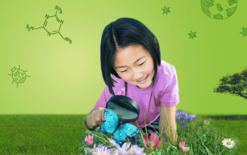 Girl on the green grass looking at a blue butterfly with a magnifying glass