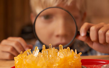 Boy looking through a magnifying glass examines an orange crystal structure
